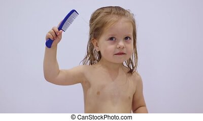 cute little blonde girl combing her hair with a blue comb on white background. hair care. parenting. independence. FullHD footage.