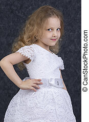 Cute little blonde girl in a beautiful white dress on a dark background. Six year old beautiful girl