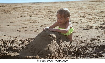 Cute little blonde girl playing with the sand at a lake