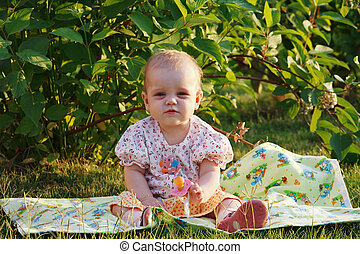 Cute little blonde girl with a pacifier sitting on a meadow