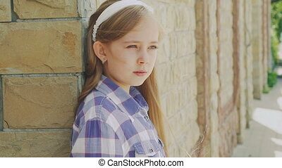 Cute little blonde looking at camera near the building. Slowly