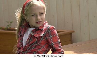 Cute little blonde looking at camera when her hair moving. Slowly