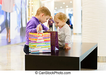 Cute little boy and girl inspecting shopping bags in mall