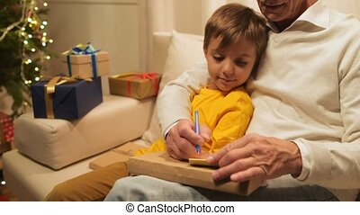 Cute little boy and his senior grandfather signing Christmas presents