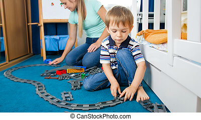 Cute little boy and his young mother playing with toy railroad on floor at bedroom
