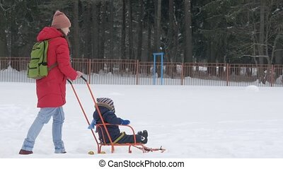 Cute little boy and young mother play in the winter with snow in the park. Blue kid's jacket and red at mom.
