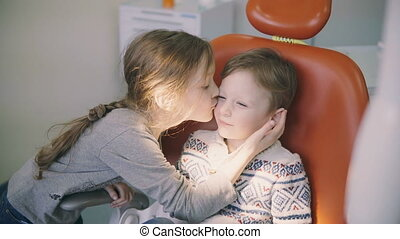 Cute little boy before the doctor reception. Girl kisses...
