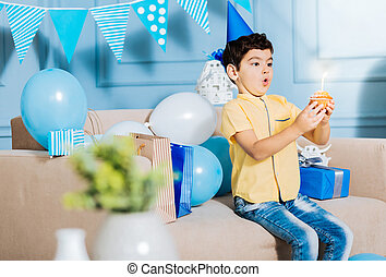 Cute little boy blowing out a candle on birthday muffin -...
