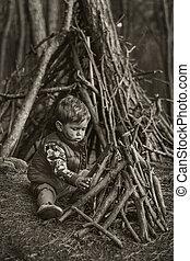 Cute little boy building a wooden hut