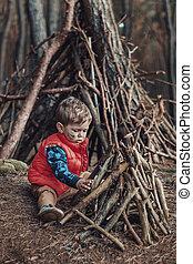 Cute little boy building a wooden shelter