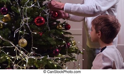 Cute little boy decorating Christmas tree with his grandfather