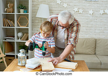 Cute Little Boy Drilling Wood with Help from Grandpa