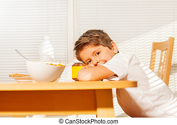 Cute little boy during breakfast in the kitchen
