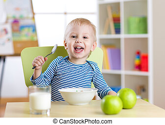 cute little boy eating cereal with the milk in nursery