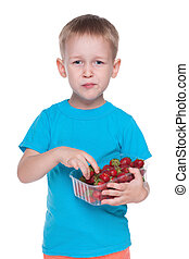 Cute little boy eats strawberry
