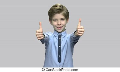 Cute little boy giving thumbs up. Cheerful boy in stylish...