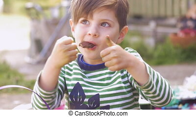 Cute little boy giving thumbs up while enjoying eating...