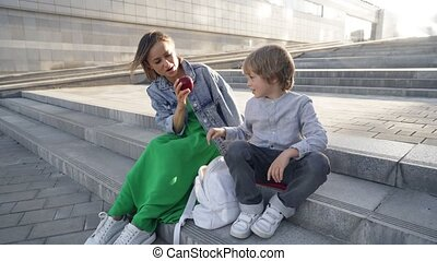 Cute little boy going to school with his mother outdoors. Happy mom sitting on stairs with son, cute preteen son giving apple for his mother. Trust, family value concept