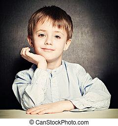 Cute Little Boy. Happy Child on Blackboard Background