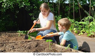 Cute little boy helping mother planting organic vegetable sprouts and digging holes in soil at garden bed with small toy shovel