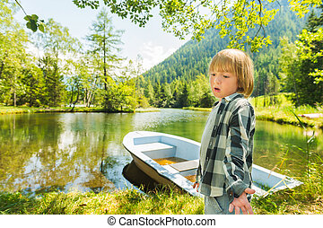 Cute little boy hiking in swiss Alps, resting by the lake