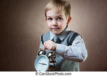 Cute little boy holding alarm clock