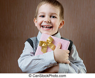 Cute little boy holding dotted present boy
