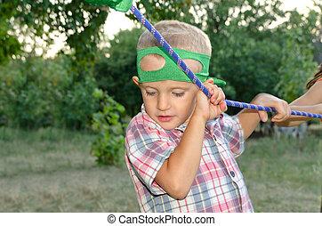 Cute little boy holding onto a purple rope