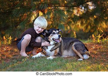 Cute Little Boy Hugging His Pet German Shepherd Mix Dog Outside