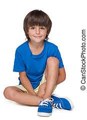 Cute little boy in a blue shirt sits