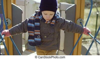 Cute little boy in orange rubber boots walking on...