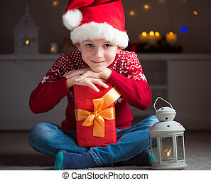 Cute little boy in red hat with gift and latern waiting Santa Claus