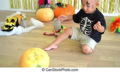 Cute little boy in skeleton costume playing with pumpkin at home