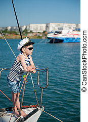 cute little boy in sunglasses and captain cap on yacht board in sea port in summer vacation day
