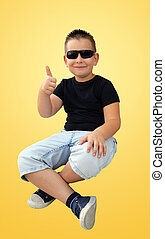 Cute little boy in sunglasses showing thumbs up