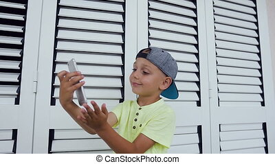 Cute little boy in t-shirt and cap doing selfie photo with smartphone at home isolated on white background. Happy teenager making selfie photo for social networks