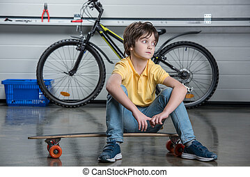Cute little boy in t-shirt and jeans sitting on skateboard and looking away