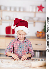 Cute little boy in the kitchen in a red Santa Hat