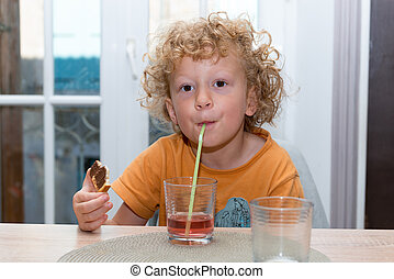 Cute little boy is drinking red juice using straw - a cute...
