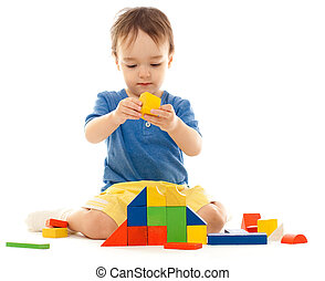 Cute little boy is playing with colorful building wooden blocks