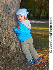 Cute little boy is playing with leaves in autumn park