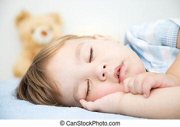 Cute little boy is sleeping in front of his teddy bear