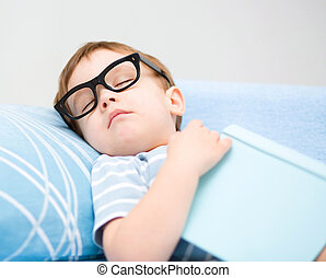 Cute little boy is sleeping while wearing glasses and put ...