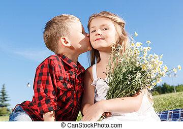 Cute little boy kissing girl