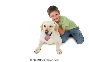 Cute little boy kneeling with his labrador smiling at camera...