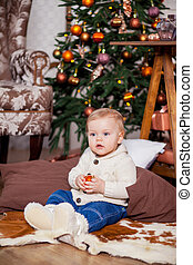 Cute little boy laughing near the Christmas tree