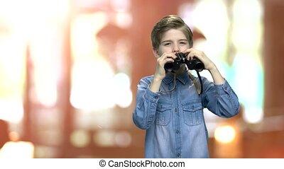 Cute little boy looking through binoculars. Caucasian child...