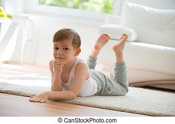Cute little boy lying on floor