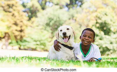 Cute little boy lying with labrador dog on a sunny day