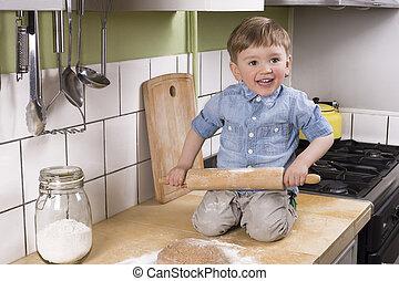 Cute little boy making pizza